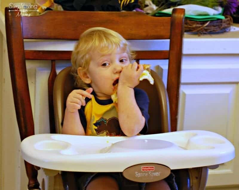 A toddler eating breakfast during his morning routine.