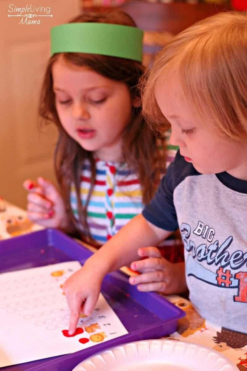 Kids finger painting apples