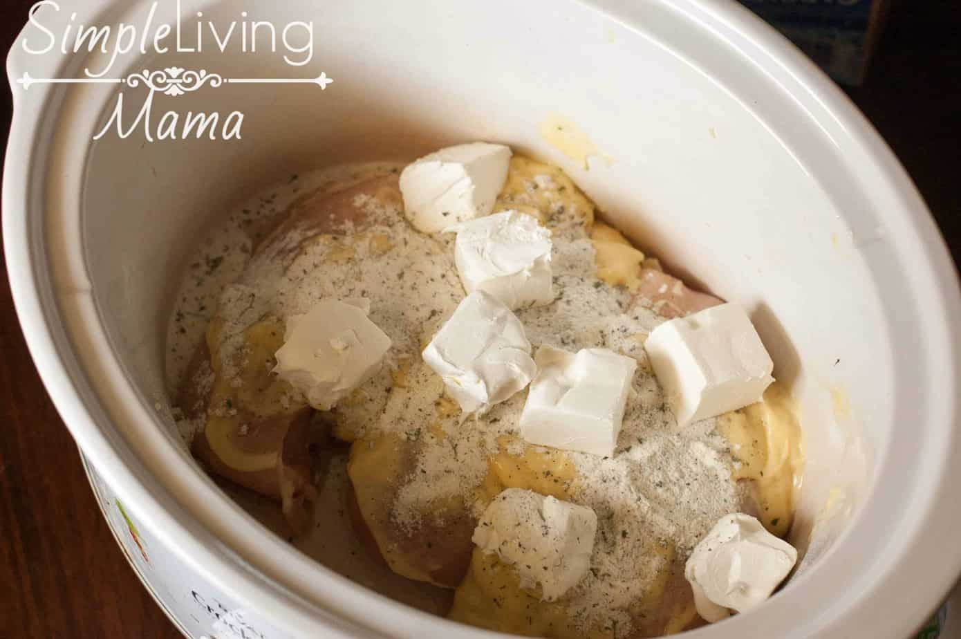 Adding cream cheese to the crock pot.